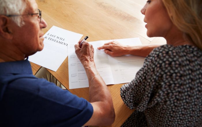 Women helping man sign will (How to Handle Key Non-Tax Financial Issues When a Loved One Passes Away)